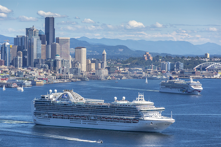 Two cruise ships departing Seattle on a sunny day with the skyline in the background.