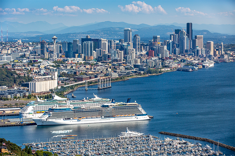 Two cruise ships docked at the Port on a sunny day with the Seattle skyline in the background.